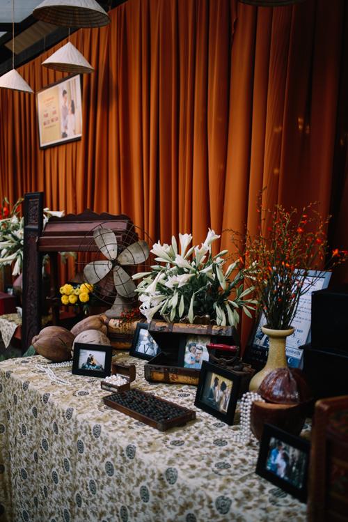 Bàn tiếp tân được tô điểm bởi bàn tính cổ, ảnh cưới của uyên ương, vòng ngọc, quạt cũ và những trái dừa.
