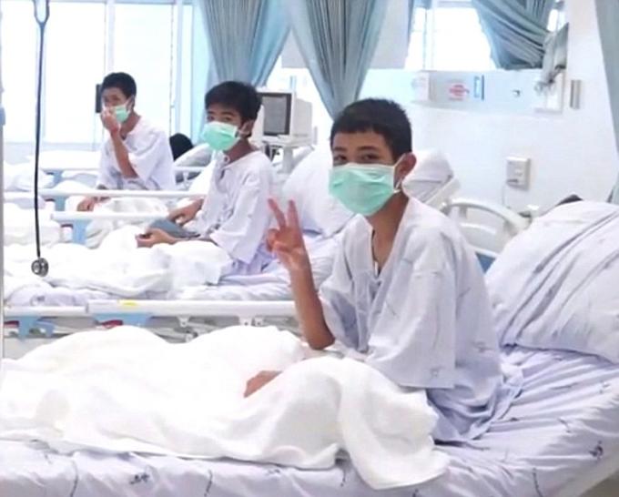 Các cậu bé vẫy chào và giơ tay thể hiện dấu hiệu hòa bình. Ảnh: AFP.