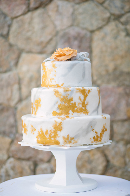 Bánh cưới ba tầngcủa uyên ương là sự kết hợp giữa vàng đồng và trắng. Trên cùng là một bông hoa hồng vàng có thể ăn được.