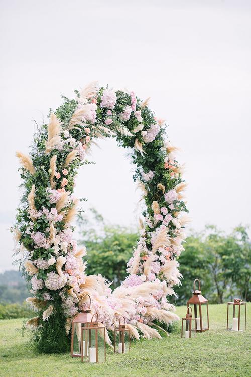 Cổng hoa được kết bằng cẩm tú cầu, cỏ bông bạc, hoa hồng và lá dương xỉ, lá cây. Wedding planner còn dựng nến trắng để không gian thêm ấn tượng. Về ý nghĩa biểu tượng, hình tròn tượng trưng cho sự hoàn thiện, vĩnh cửu, ngụ ý về mối quan hệ bền vững.