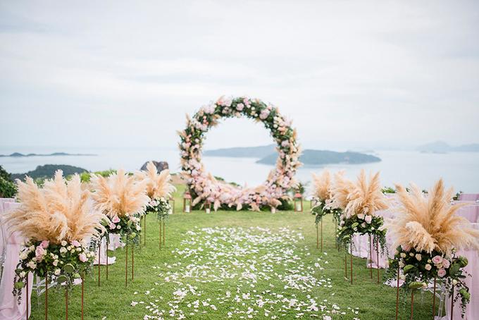 Dọc lối đi tiến vào lễ đường được rải cánh hoa hồng trắng và hai bên là những trụ hoa hồng, cỏ bông bạc. Cô dâu đã chọn bảng màu của lễ cướigồm hồng phớt và vàng hồng.
