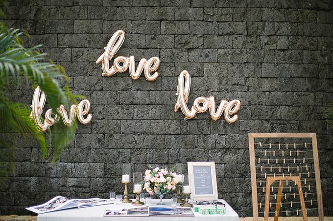 Theo xu hướng hiện nay, nhiều cô dâu chú rể sử dụng bóng bay ký tự chữ cái để thể hiện thông điệp mà họ muốn truyền tải trong đám cưới. Ở đây, Bryan và Su đã chọn từ love (tình yêu) để gửi tới khách mời. Bàn tiếp tân được bố trí khá đơn giản với giá nến, hoa hồng tươi và ảnh cưới của uyên ương.