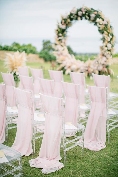 Những chiếc ghế nhựa trong suốt được trang tríbằng những dải lụa màu hồng nhạt.