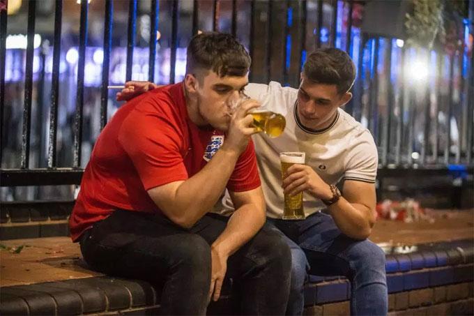 Hai CĐV chia sẻ nỗi buồn thua trận bằng bia.