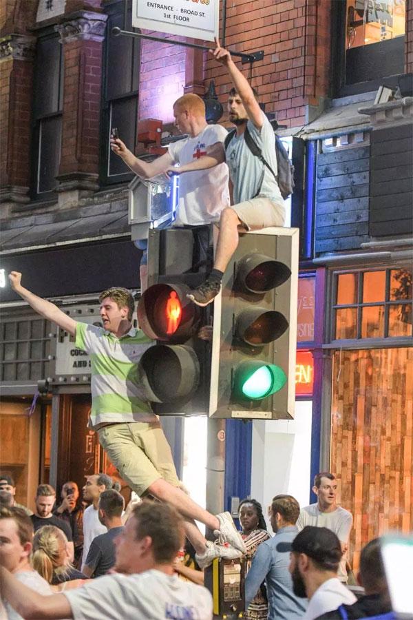 Cột đèn tín hiệu giao thông bị các CĐV cuồng trèo lên quậy phá.