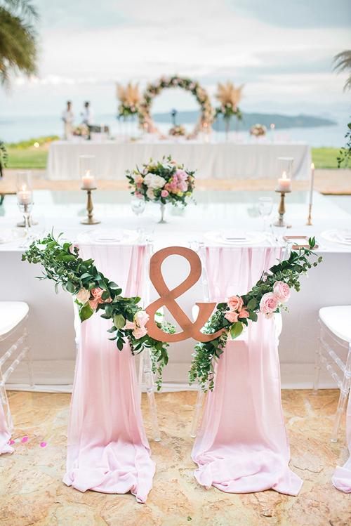 Ghế ngồi của cặp vợ chồng thêm phần đáng yêu và lãng mạn khi được tô điểm bởi dây hoa hồng.