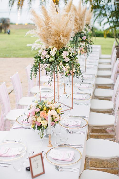 Điểm nhấn của bàn tiệc tập trung vào trụ hoa cao. Mặt khác wedding plannercòn sử dụng giá nến và bình hoa nhỏ để tạo nên nét ấn tượng cho bàn tiệc.