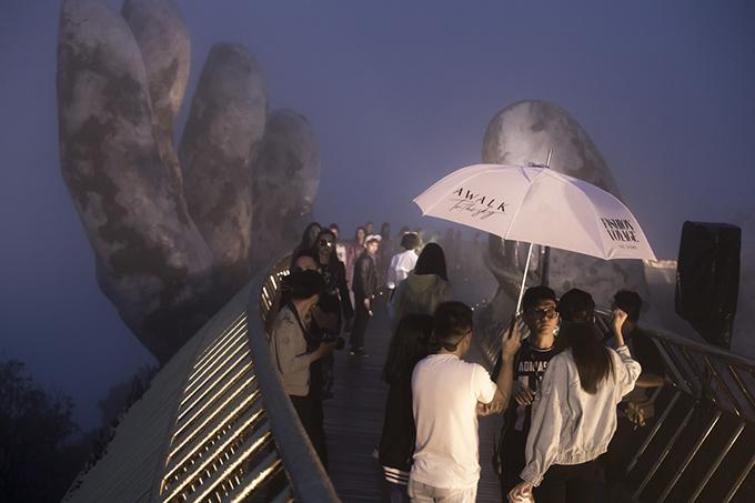 Sàn diễn thời trang được bố trí trên Cầu Vàng ở Bà Nà, tuy nhiên thời tiết mưa gió đã mang lại nhiều khó khăn so với dự kiến ban đầu.