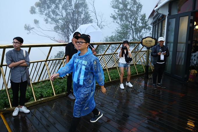 Đạo diễn Long Kan mặc áo mưa khi điều khiển chương trình.