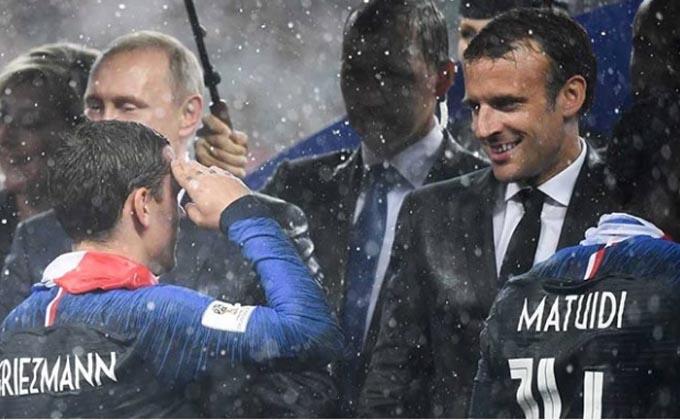 Ông Macron đội mưa chúc mừng và trao huy chương cho các cầu thủ Pháp. Ảnh: NDTV.