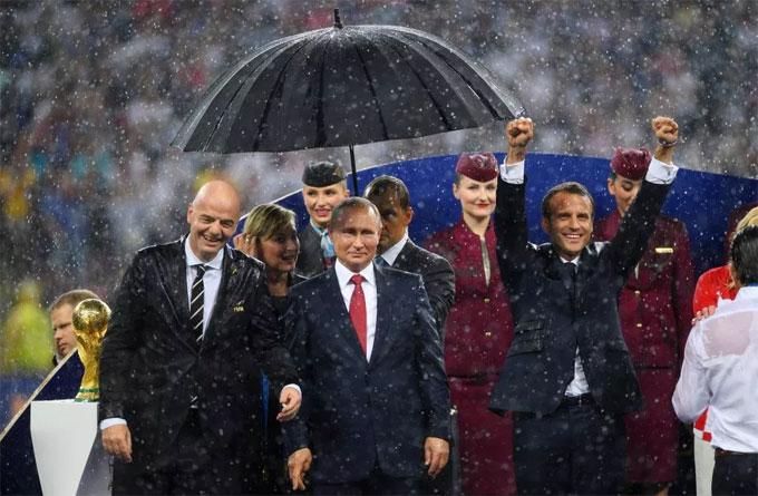 Ông Putin đứng cạnh Chủ tịch FIFA Gianni Infantino và Tổng thống phápEmmanuel Macron trên bục trao huy chương World Cup. Trong khi ông Putin khá điềm tĩnh chờ đến màn trao giải, người đồng cấp Macron phấn khích vì chiến thắng của đội nhà.