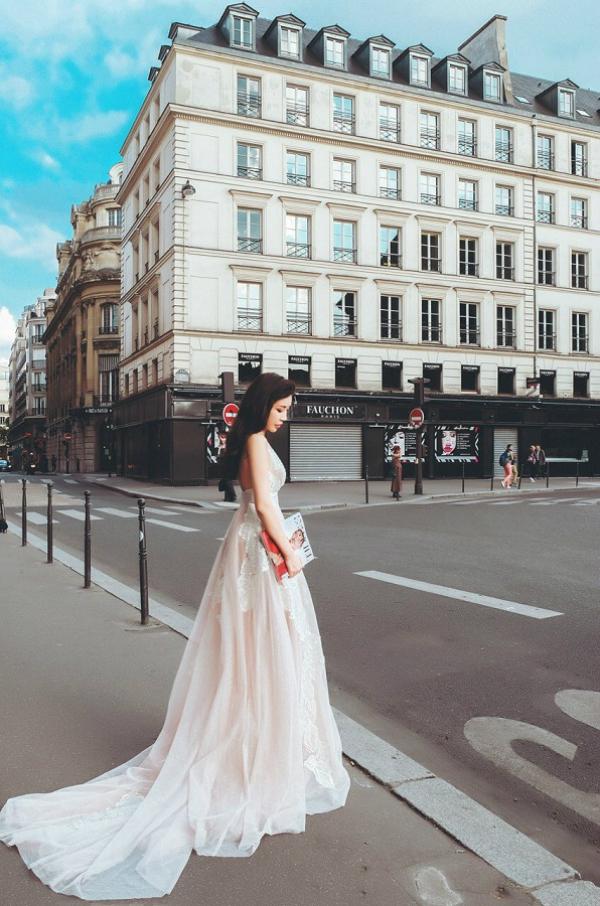 Thiết kế với phần thân và đuôi váy dài thướt tha từ chất liệu voan cao cấp sang trọng mang đến vẻ nữ tính mềm mại và đầy cuốn hút . Kết cấu đường xẻ sâu chữ V khiến Lam Cúc quyến rũ trong khung cảnh hoa lệ của Paris.