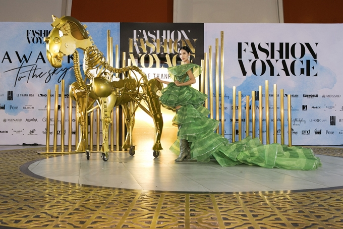 Hoàng Thùy tạo dáng ấn tượng bên linh vật của show diễn. Bộ váy khá cồng kềnh nhưng nhờ kinh nghiệm có được tại các sàn diễn quốc tế, cô đã thể hiện xuất sắc thiết kế đặc sắc này.