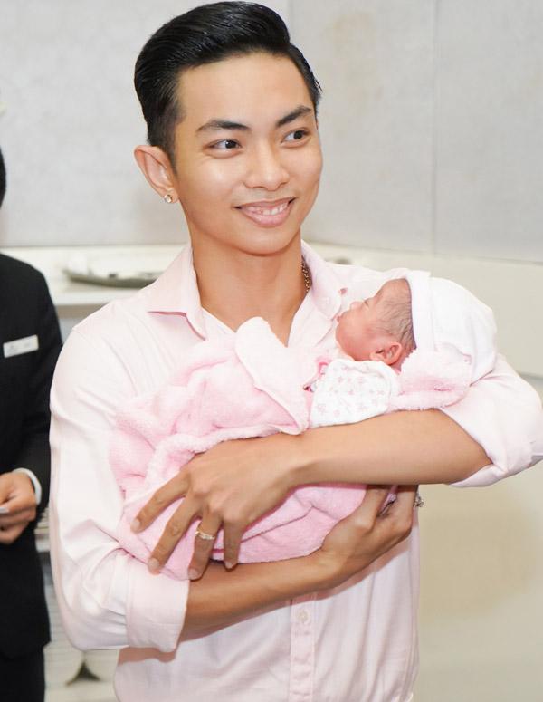 Phan Hiển ôm trọn con gái trong lòng, miệng cười không ngớt khi bế con đi chào hỏi bạn bè.