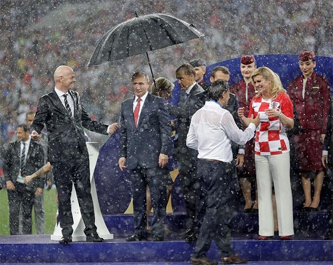 Tổng thống Putin một mình được che ô. Ảnh: Twitter.
