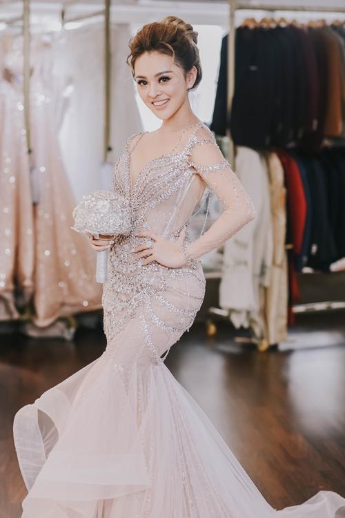 Váy được hoàn thiện, Trang ngất ngây bởi gam màu phớt hồng lãng mạn và đặc biệt là những chi tiết đính kết kỳ công. Dáng váy đuôi cá cách điệu với phần chân xòe xếp nếp như từng lớp bọt sóng, mềm mại, thướt tha. Thiết kế này cũng giúp cô dâu dễ dàng di chuyển hơn.