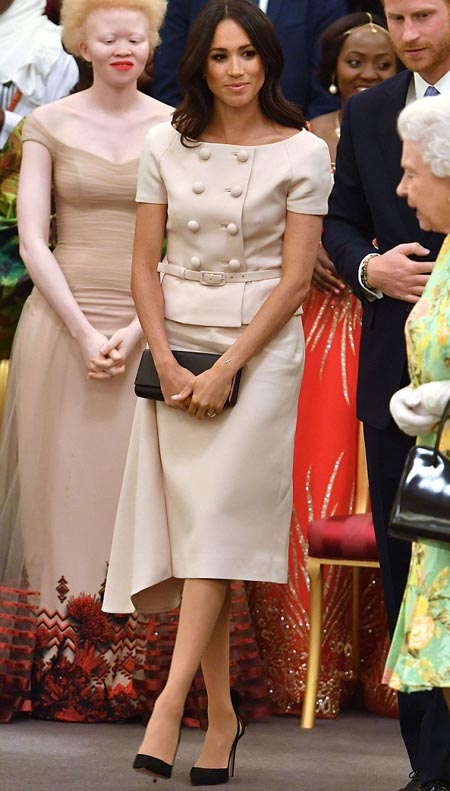 Preened in Prada   Another date with Her Majesty  this time with Harry in tow  at the Young Leaders Awards Ceremony at Buckingham Palace, and once again, the Duchess turned to a suitably high-end designer.  Her double-breasted, belted blouse and her matching skirt are both by Prada, totalling £2,100, as is her black clutch bag, which retails for £1,280.  Her black suede stilettos are by Aquazzura (£490).  And no outfit would be complete without a bit of subtle bling: Meghan finished her look with gold and diamond earrings by Vanessa Tugendhaft (£900), as well as a diamond cross bracelet by the same designer (£525), a token to mark her Church of England baptism earlier in the year.Cost: £5,295