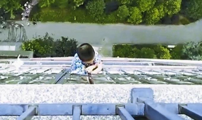 Cậu bé kiên cường bám vào lan can tầng dưới để giữ mạng trước khi được những người khác đến cứu. Ảnh: SCMP.