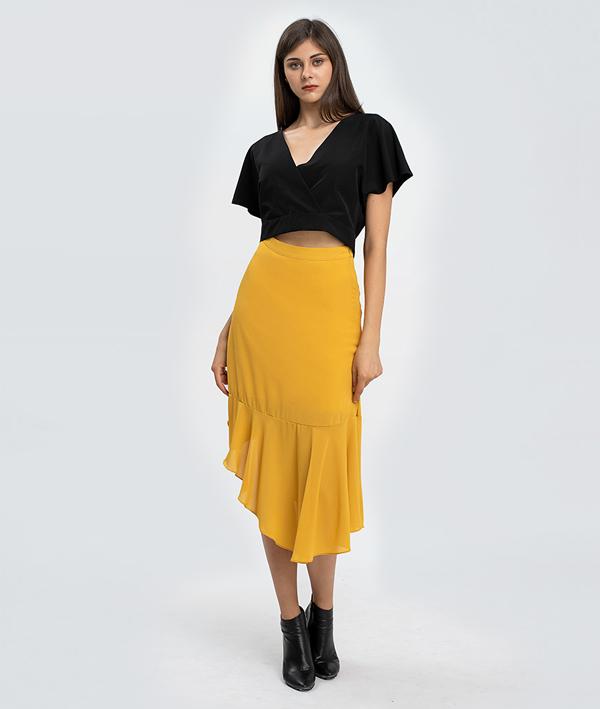 Trong một cách mix đồ khác, bạn có thể phốiáo phom rộng màu đen với chân váy vàng cá tính. Chiếc áo được thiết kế tinh tếvừa che khéo đi bắp tay kém thon, vừa tôn nétgợi cảm với phần eo hở.