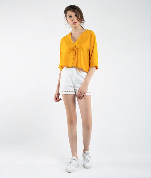 Một trong những tông màu không thể thiếu trong mùa hè chínhsắcvàng nổi bật. Với chiếc áo croptop cổ chữ V màu vàng hợp xu hướng, các quý cô có thể kết hợp với quần short trắng hay chân váy điệu đà mà không sợ set đồ bị nhàm chán, đơn điệu.