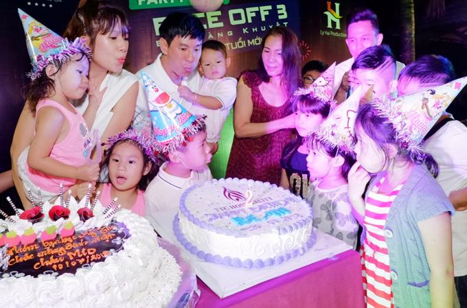 Hai vợ chồng cùng các con thổi nến mừng sinh nhật cậu út Mio trên bãi biển.