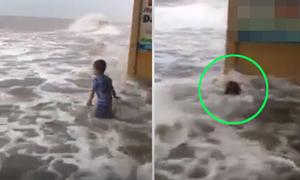 Mẹ mải quay video, con trai bị sóng biển động xô ngã