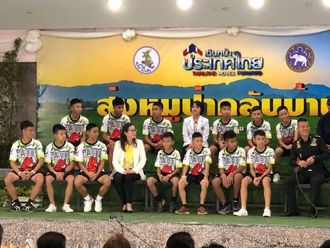 12 thiếu niên và huấn luyện viên trẻ (ngồi ngoài cùng bên trái hàng dưới) xuất hiện đầy đủ tại họp báo.