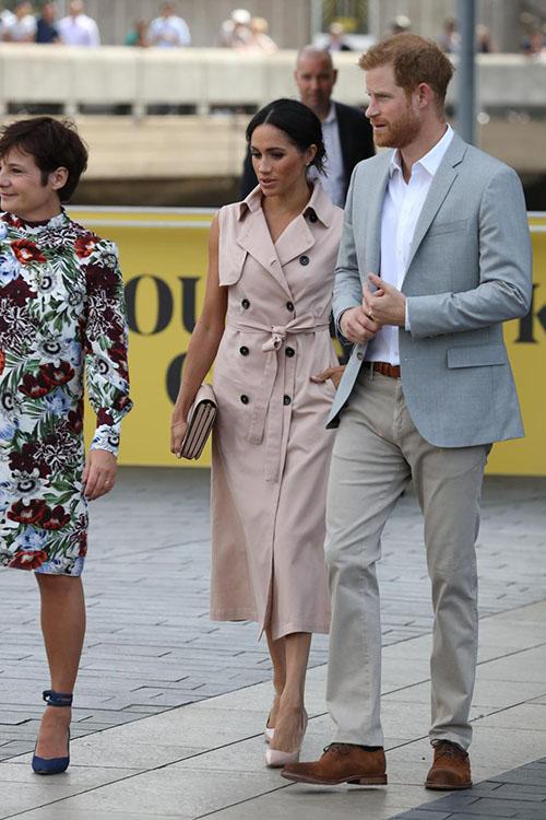 Xuất hiện ở sự kiện, nữ Công tước xứ Sussex diện một chiếc váy màu hồng nhạt, trị giá 626 bảng Anh (820 USD) của House of Nonie, kết hợp giày cao gót cùng tông màu. Trong khi đó, Hoàng tử Harry bảnh bao khi diện vest màu xám sánh vai vợ mới cưới.