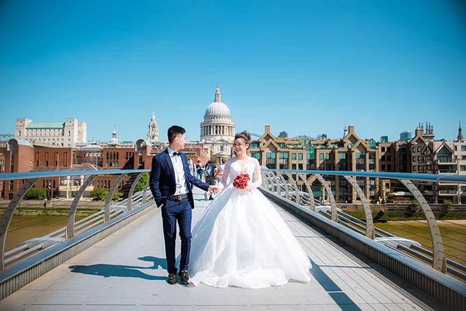 Cả hai cùng dạo bước trên cầu dành cho người đi bộ. Cô dâu cầm theo bó hoa cưới kết từ hồng đỏ để tạo điểm nhấn cho bức ảnh.