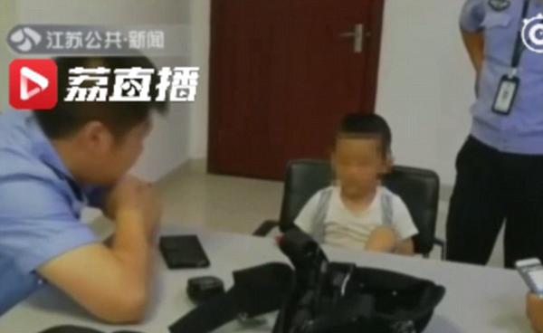 Kaikai ở đồn cảnh sát chờ bố tới đón. Ảnh: Jiangsu TV.