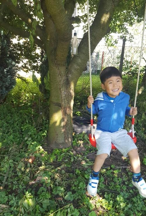 Cậu con trai 5 tuổi của chị Thủy nô đùa dưới bóng mát cây ăn trái trong vườn mẹ.