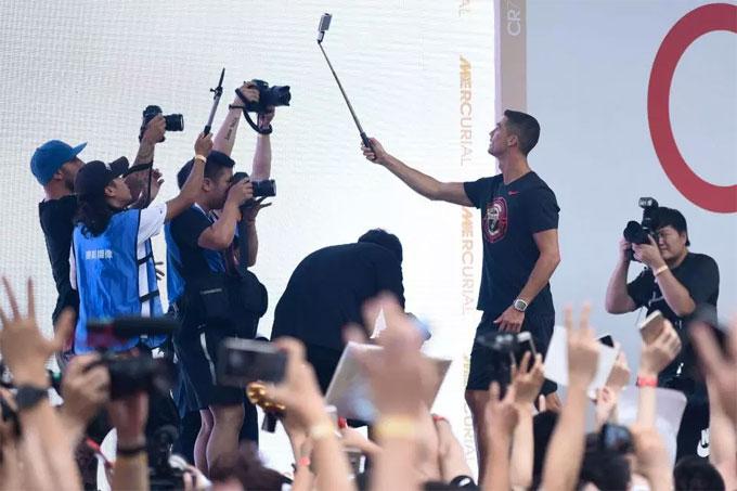 C. Ronaldo nhiệt tình giao lưu với CĐV dùng gậy tự sướng để chụp selfie. Trung Quốc là thị trường lớn và C. Ronaldo thường xuyên đến đây quảng bá.