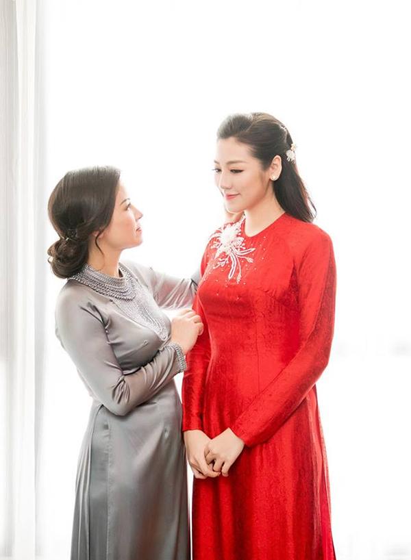 Mẹ Tú Anh đẹp thanh lịch trong bộ áo dài màu xám, sửa sang tóc mai cho con gái.