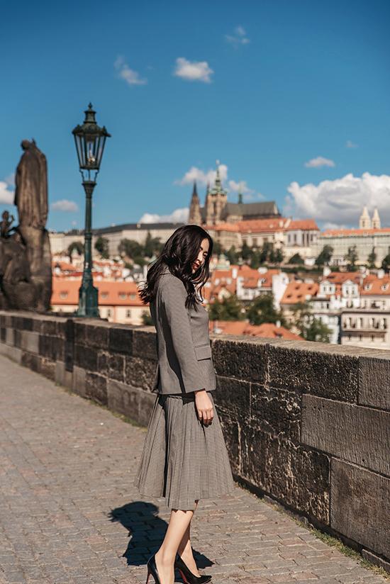 Kết hợp cùng áo vest trang trí nơ bướm xinh xắn là chân váy midi xếp ly tỉ mỉ.