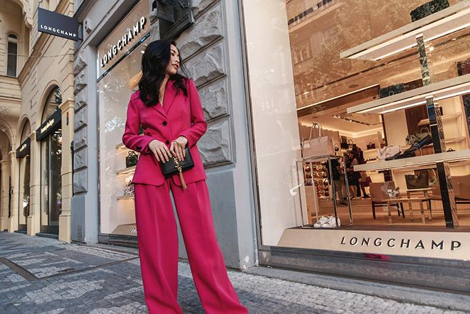 Clutch kiểu dáng sang trọng của Yves Saint Laurent tạo điểm nhấn cho bộ suit tông hồng nổi bật.