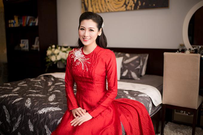 Ở lễ rước dâu diễn ra chiều 21/7, Tú Anh diện bộ áo dài đỏ thêu hoa do Hoa hậu Ngọc Hân may tặng. Cô kết hợp trang phục truyền thống với kiểu tóc xoăn nhẹ, buộc nửa và khuyên tai đính đá để hoàn thiện vẻ ngoài trong trọng đại.