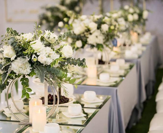 Nhà gái sử dụng các loại hoa nhập khẩu cao cấp để trang trí cho bữa tiệc. Những cây nến trắng được sắp xếp trên bàn tiệc khiến không gian thêm ấm cúng.