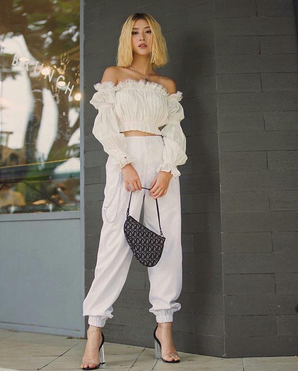 Quỳnh Anh Shyn chọn túi yên ngựa của Dior, sandal nhựa trong để tạo điểm nhấn cho set đồ tiệp sắc trắng.
