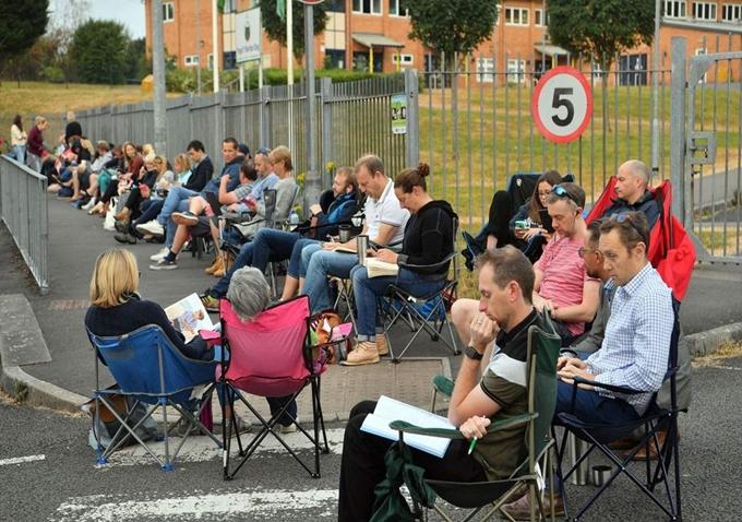 Phụ huynh xếp hàng trước cổng trường, mang theo ghế cắm trại, đồ ăn nhẹ và nước uống.