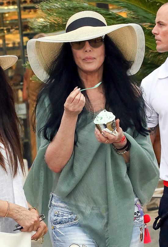 Cher vừa đi vừa thưởng thức cốc kem. Dù không trang điểm, trông bà vẫn rất xinh đẹp, duyên dáng.