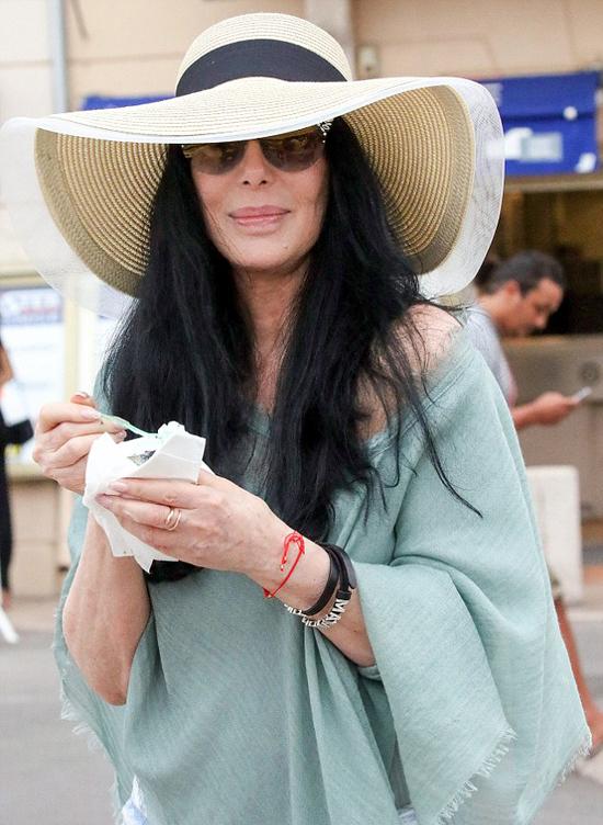 Cher vui vẻ tản bộ ở đảo St Trope hôm chủ nhật, 22/7. Dù đeo kính râm và đội mũ rộng vành, danh ca người Mỹ vẫn dễ dàng được nhận ra với mái tóc đen suôn dài đặc trưng.