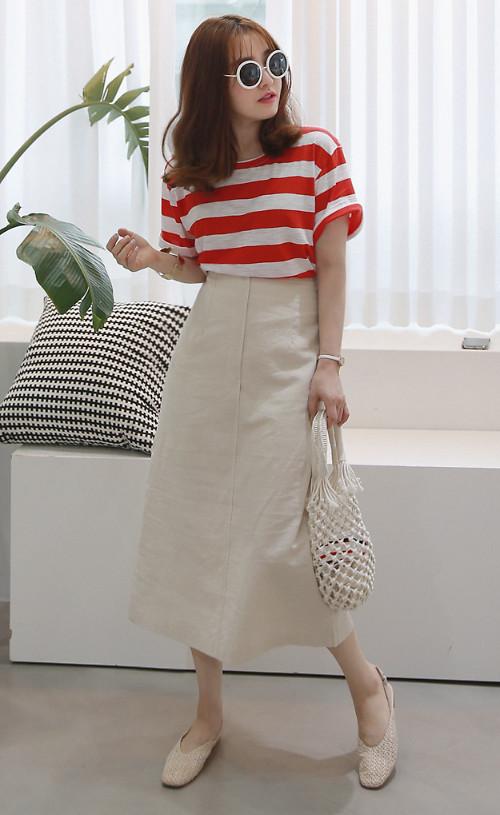 Áo thun kẻ sọc đỏ trắng trở thành điểm nhấn nổi bật cho set đồ gồm chân váy midi, túi dây đan thủ công và giầy đế bệt.