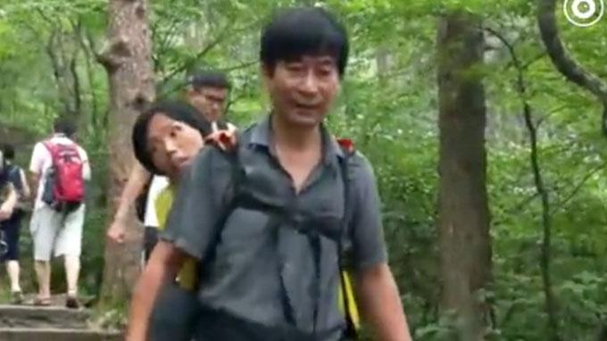 Ông Wang cõng vợ bước từ trên đỉnh Huangshan, tỉnh An Huy, xuống chân núi hôm 23/7. Ảnh: SCMP.