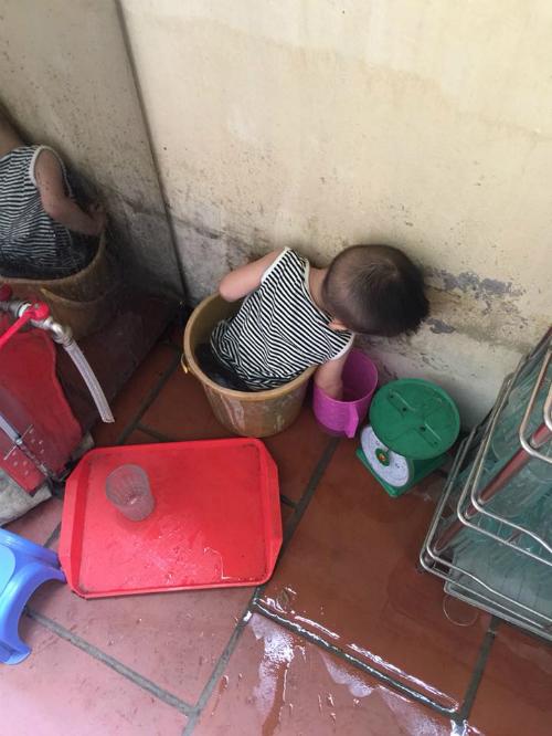 Bé Bon trèo vào cả thùng nước cao mẹ đang rửa chén để nghich nước.
