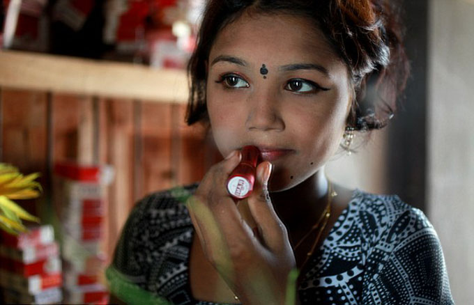 Underage sex worker Bristi applying heavy makeup to appear more mature for her evening clients at Bangladeshs largest brothel in Daulatdia