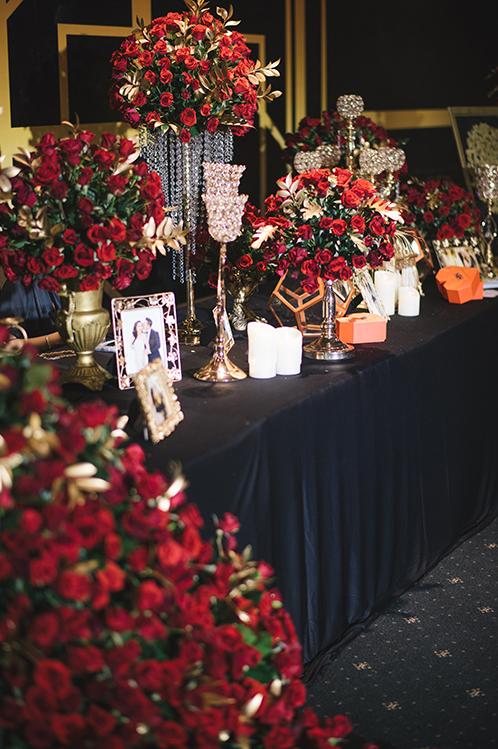 Giá nến, bình hoa rủ, ảnh cưới của cặp vợ chồng được đặt tại góc khác của bàn tiếp tân.
