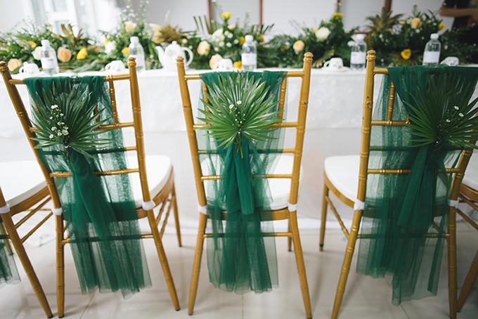 Ghế ngồi của khách mời được gắn dải lụa xanh và lá cọ cùng tông. Theo lý giải của wedding planner, phong cách rừng nhiệt đới đem đến cho khách mời sự thư giãn, thoải mái, gần gũi với thiên nhiên, phù hợp với tính cách của cô dâu và chú rể.