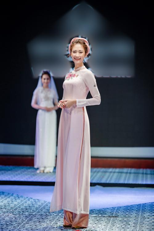 2. Áo dàimàu sắc nhẹ nhàng: Sắc đỏrực rỡ của cánh hoa trên nền vải hồng nhạt khiến người mặc vừanhẹ nhàng, nữ tính màhiện đại. Cô dâu diện quần màu cà phê sữa để kết hợp cùng áo dài.