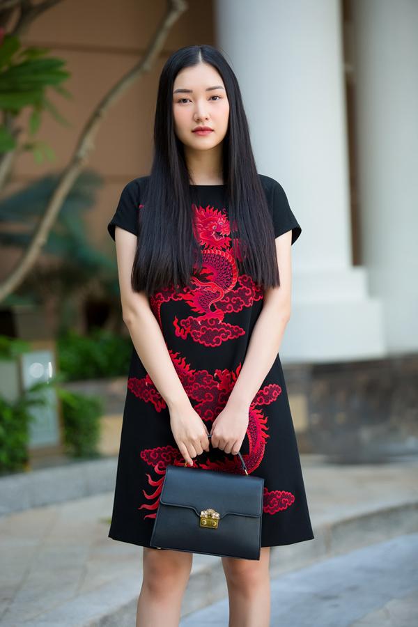 Nàng thơ xứ Huế Ngọc Trân sinh năm 1995, kém Ngọc Khánh 19 tuổi và kém Diễm My 33 tuổi. Cô chọn đầm suông có họa tiết rồng màu đỏ trẻ trung hơn.