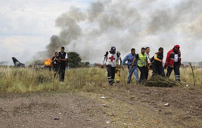 Nhân viên cấp cứu quấn tấm lá cách nhiệt quanh một người bị thương nặng trong vụ tai nạn.